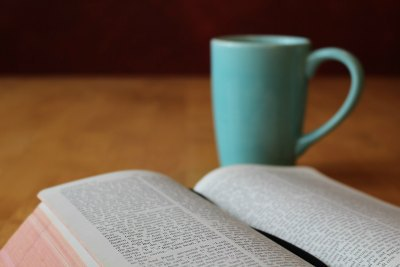 Bible with teal coffee cup to research work ethic.